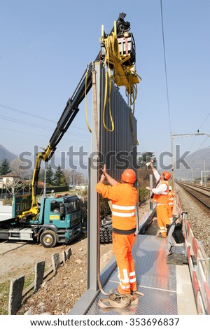 Capolago, Switzerland - 14 march 2012: Workers install noise barriers at the railway in Capolago, Switzerland