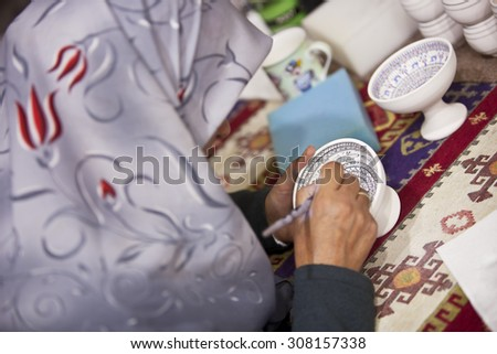 CAPPADOCIA, TURKEY  APRIL 17: Woman decorates a ceramic bowl with designs typical to the region on April 17, 2012 in Cappadocia, Turkey. - stock photo
