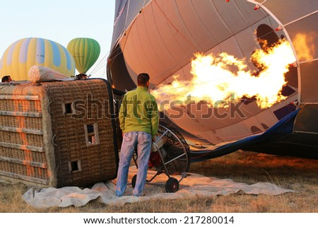 Cappadocia, Turkey - August, 10 2013 :  Ground Crew inflating Hot Air Balloon before launching.  - stock photo