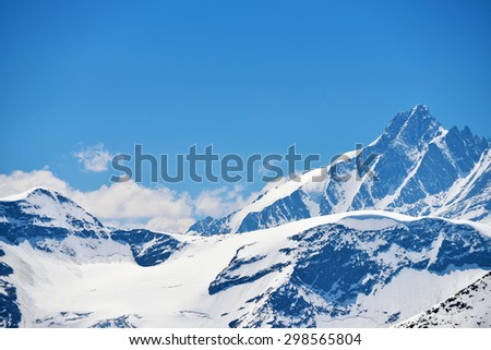 capped mountain peaks and blue sky - stock photo