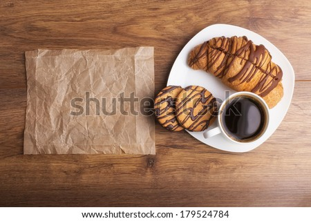Cappuccino and croissant on wooden table - stock photo