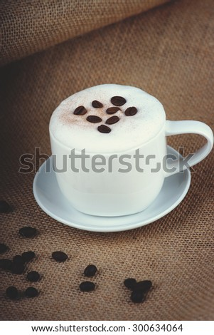 Cappuccino coffee cup and coffee beans on burlap sack
