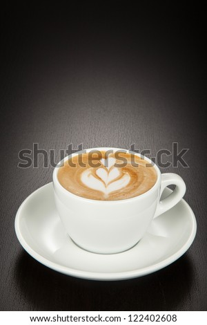 Cappuccino coffee in a white cup and saucer on a black wooden background. - stock photo