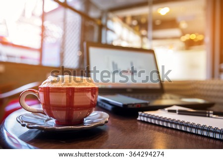 cappuccino coffee in red cup with investment report on laptop, coffee shop background  - stock photo