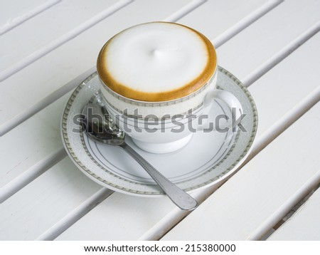cappuccino coffee in white cup on wooden background - stock photo