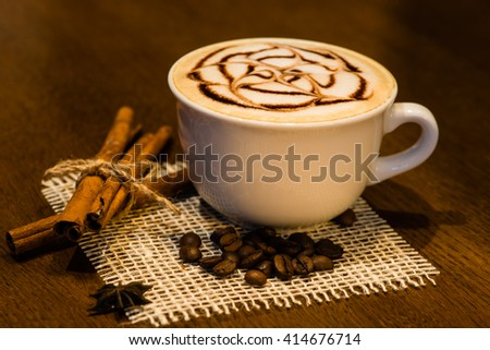 cappuccino coffee on a wooden table, coffee beans, chocolate, cinnamon - stock photo