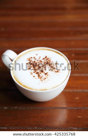 cappuccino coffee on wood background in coffee shop