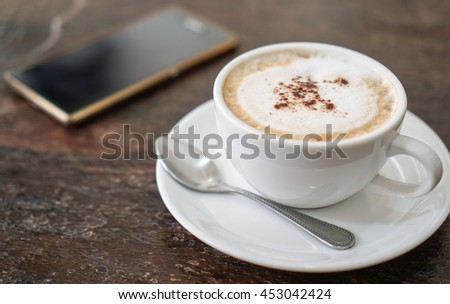 Cappuccino coffee on wood table and mobile devices background in coffee shop and relax