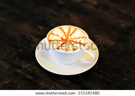 Cappuccino coffee over wooden table - stock photo