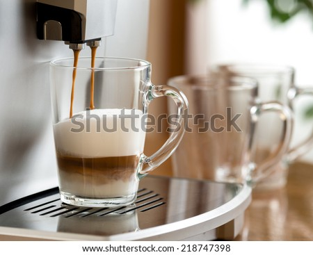 cappuccino coffee preparing in glass cup with help of machine - stock photo