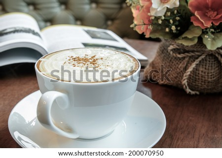 Cappuccino coffee with flowers bouquet - stock photo