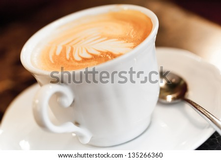Cappuccino coffee with spice and artistic foam in a white cup - stock photo