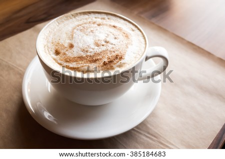 Cappuccino. Cup of coffee with milk foam stands over old paper on wooden table in cafeteria