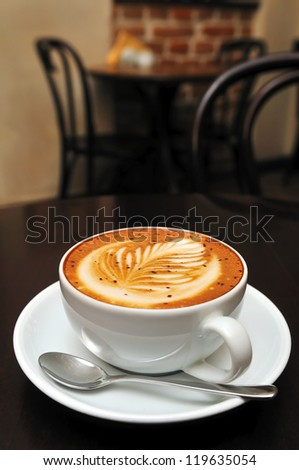 cappuccino cup on the dark brown table - stock photo