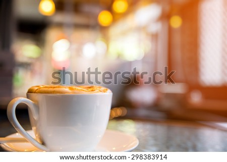 Cappuccino cup on the table, blur coffee shop background  - stock photo