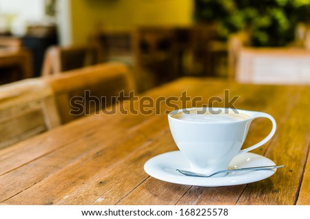 Cappuccino cup on wood table in coffee shop - stock photo