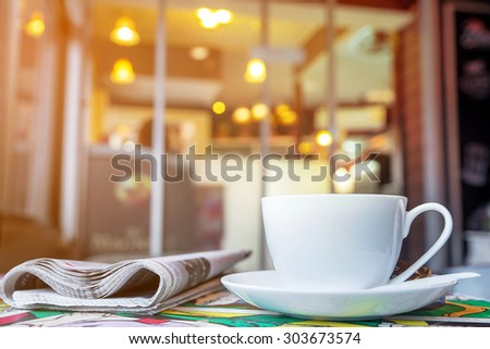 Cappuccino cup with blur coffee shop background, warm tone  - stock photo