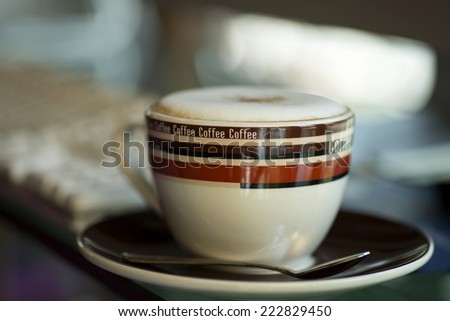 Cappuccino cup with computer and newspaper - stock photo