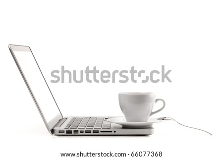 Cappuccino cup with spoon on laptop. Isolated on white background - stock photo