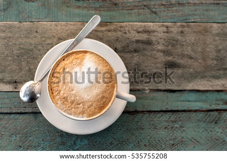 Cappuccino cup with spoon  on old rustic wooden table background. Photo taken outdoors in tuscan cafe. Top view.