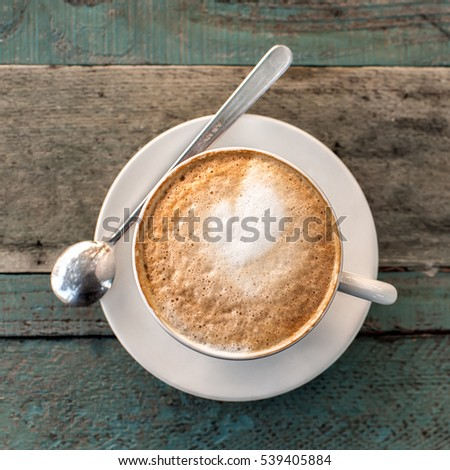 Cappuccino cup with spoon  on old rustic wooden table background. Photo taken outdoors in tuscan cafe. Top view. Square composition.