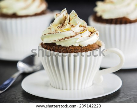 Cappuccino cupcakes in white cups. - stock photo