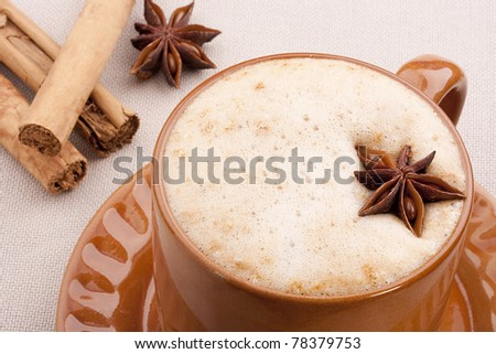 Cappuccino in a brown ceramic cup with spice. - stock photo