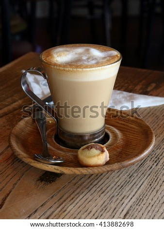 Cappuccino in a clear glass mug, on a wooden saucer with a small cookie - stock photo