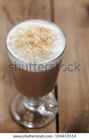 Cappuccino in a clear glass mug with caramel sprinkled on top