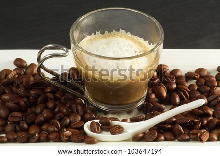 cappuccino in a glass cup over ceramic tray with beans - stock photo