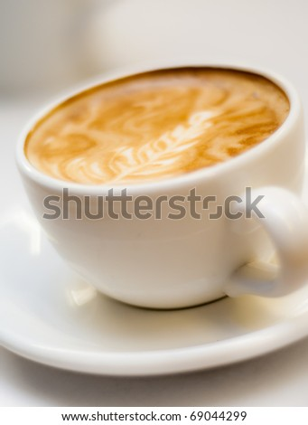 Cappuccino in a porcelin cup with rosetta design - stock photo