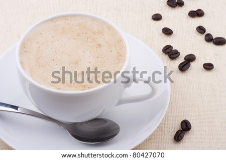 Cappuccino in a white ceramic cup with coffee grains.