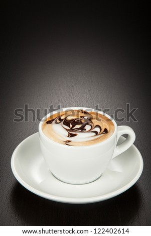 Cappuccino in a white cup and saucer on a black wooden background. - stock photo
