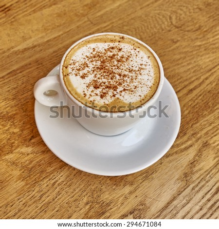 Cappuccino in white cup close-up on wood background