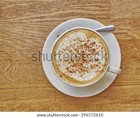 Cappuccino in white cup close-up on wood background, some space for typing - stock photo