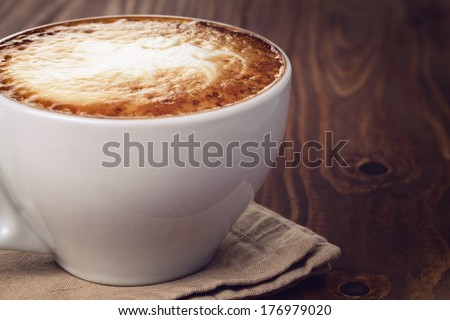 cappuccino on old wood table, vintage toned photo - stock photo