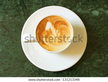 Cappuccino or latte coffee on table - stock photo
