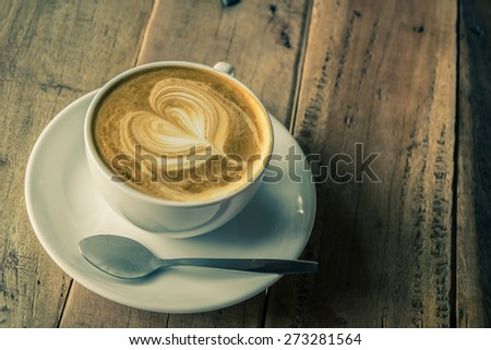 Cappuccino or latte coffee on wooden table in vintage tone style. - stock photo