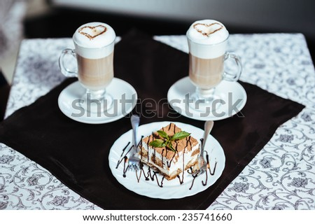Cappuccino or latte coffee with heart shape. A cup of Coffee latte with heart design. Two cups of coffee on the table, latte art. cake on the plate - stock photo