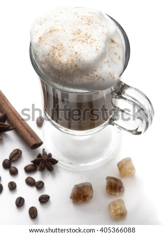 Cappuccino or latte, popular hot drink of the day. With thick milk foam and cinnamon. Decorated coffee beans, spices and caramel. Frappe clear glass on the white background, top view.  - stock photo