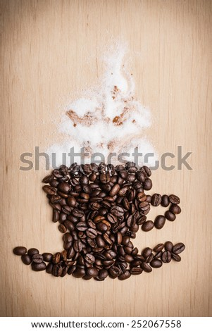 Cappuccino time. Roasted coffee beans placed in shape of cup and saucer with cinnamon white froth on wooden surface background - stock photo