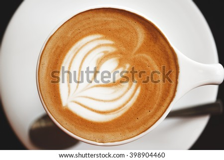 Cappuccino with beautiful foam and spoon in white cup. Latte art, top view. - stock photo