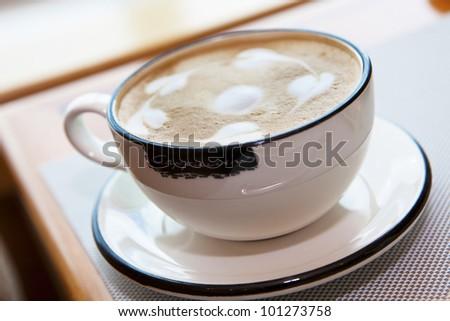 cappuccino with beautiful pattern on milk foam. Closeup - stock photo