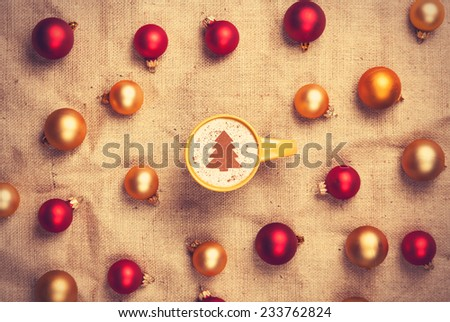 cappuccino with christmas tree shape and with red and gold christmas balls on jute background.