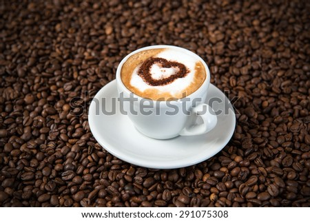 cappuccino with heart on a lot of coffee beans  - stock photo