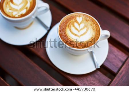 Cappuccino with latte art on wooden table. - stock photo