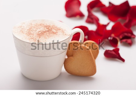Cappuccino with love. Closeup image of lovely heart shape cookie and an exquisite cup of cappuccino arranged with copy space on white background and decorated with rose petals - stock photo