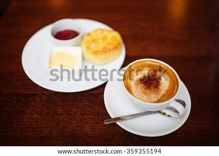 Cappuccino with Scottish Scone out of focus in the back.  - stock photo