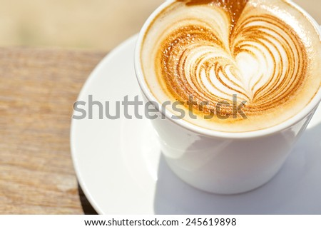Cappuchino or latte coffe in a white cup  with heart shaped foam on wooden board - stock photo