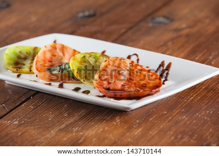 Caprese Appetizer; sliced tomatoes, mozzarella, basil drizzled with a balsamic vinaigrette. - stock photo